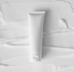 Mockup white plastic tube for moisturizer, lotion, facial cleanser or shampoo on smudged cream texture background top view. Delicate purity skin care product