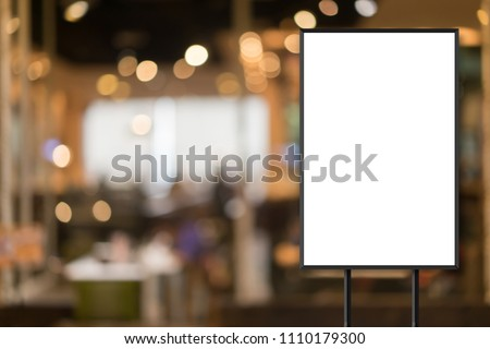 mockup white poster with black frame stand in front of blur restaurant cafe background for show or present promotion product concept #1110179300
