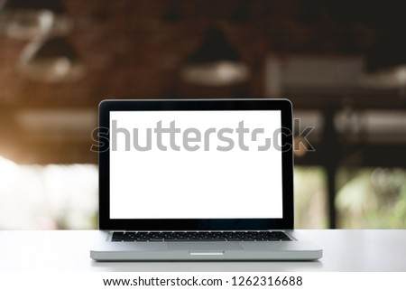 Mockup with blank screen laptop on Empty space white computer table,Interior office blurred background of bokeh.