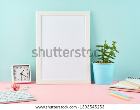 Mockup with blank white frame, alarm, notepad, cup of coffee on pink table against blue wall with copy space