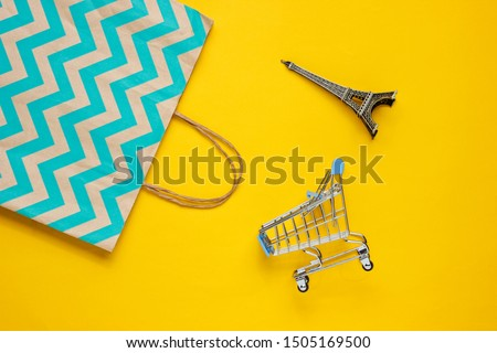 Mockup with shopping cart and paper bag on yellow background. Happy customer concept. Internet shopping. Online store. Consumerism, lifestyle