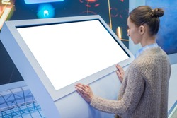 Mockup: woman looking at blank white interactive touchscreen display of electronic kiosk at technology exhibition, museum. Mock up, copyspace, template, isolated, white screen, futuristic concept