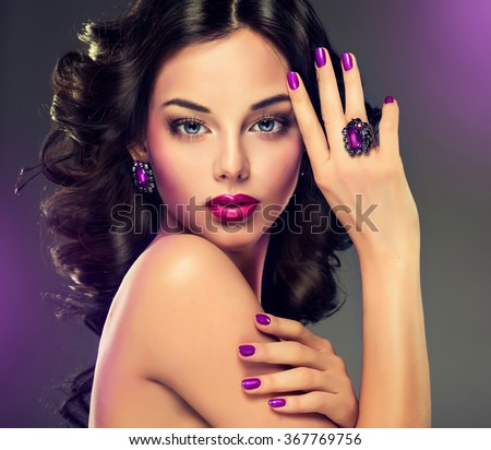 Model curly hair and jewelry , violet makeup , manicure on nails .  elegant hairstyle . Fashionable jewelry set , ring and earrings .