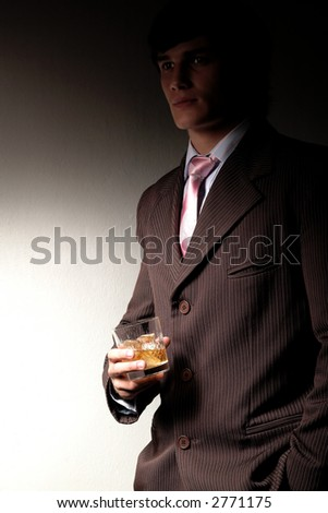 Model dressed in business suit with a glass of whiskey in his hand