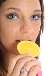 model eating an orange slice upclose