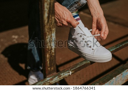 Model hands fixing laces on a white sneaker Stockfoto ©