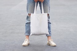 model hold blank white fabric tote bag for save environment on street fashion