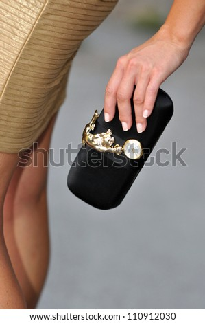 Model holding couture designer purse with watch on it