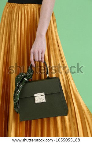 Model holds fashion handbag