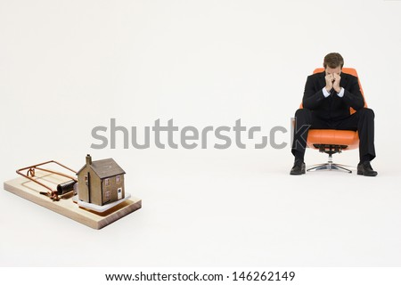 Model home on mouse trap with worried businessman sitting on chair representing increasing real estate rates #146262149