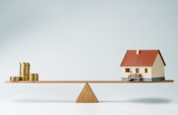 Model house and money coins balancing on a seesaw