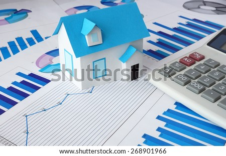 Model  house for sale and graphs. Real estate concept.