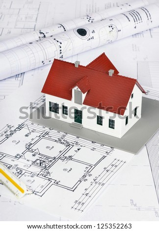 model house on a construction plan for house building - stock photo