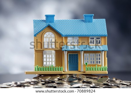 Model house on a pile of coins.