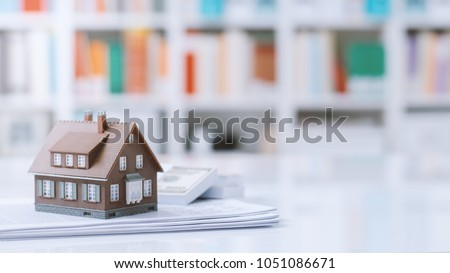 Model house, paperwork and cash money on a desktop: real estate, home loan and investments concept