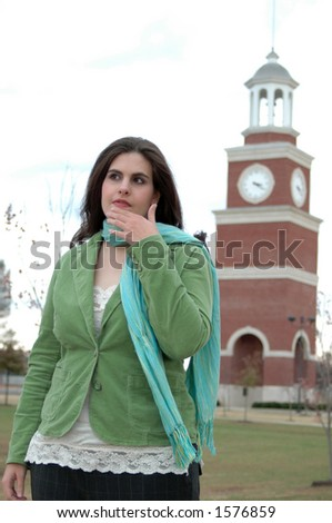 Model in front of clock tower. Conceptual shot for decision making, confusion, uncertainty. - stock photo