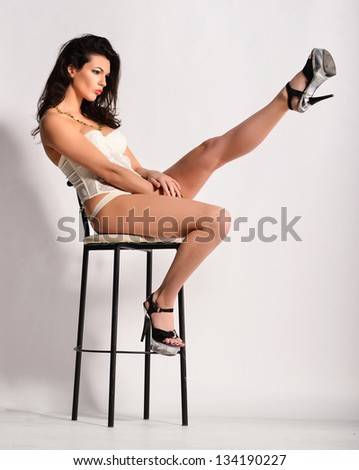 Model in lingerie sitting on high chair