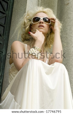 Model in long white dress wearing white sunglasses on a sunny day