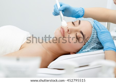 Model lying on couch with closed eyes. Hand in blue glove touching patient\'s face with brush. Cosmetological clinic. Healthcare, clinic, cosmetology