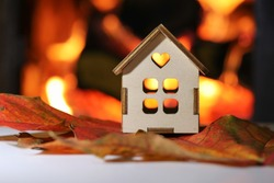 Model of a house on a background of fire.The concept of comfort and warmth in the house.