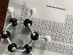 Model of a molecule of Benzene (C6H6) with a copy of the Periodic Table of Elements. The chemical compound is considered a hydrocarbon.