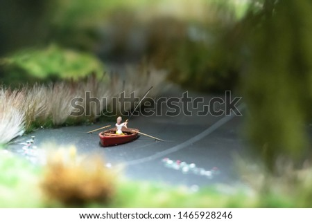 Model of a pond with a boat and a fisherman. A fisherman catches a fish. #1465928246