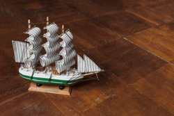 model of an old sailing ship on a scratched wooden surface. Beautiful miniature ship. Wooden ship figurine. Antique model sailing ship isolated with clipping path.