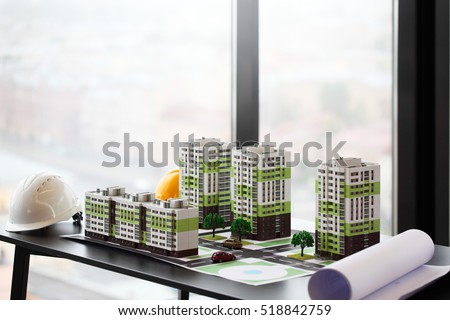 Model of apartment house, blueprint and hardhat on table in office