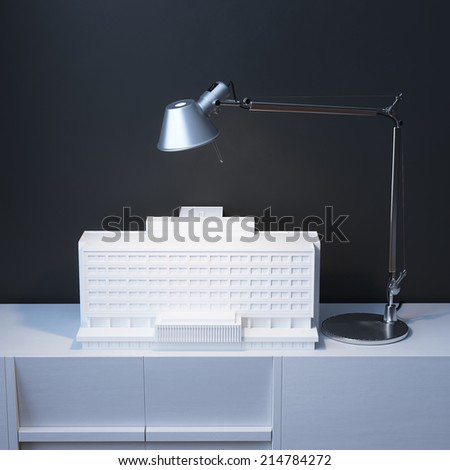 Model Of Building Under The Lamp On The Desk In Minimalist Interior