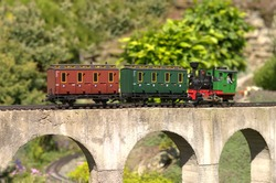 Model of locomotive pushing carriages on a concrete viaduct bridge