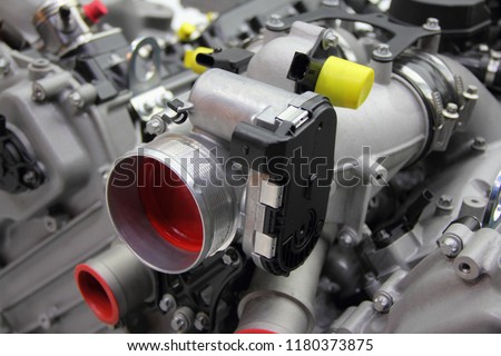 Model of new car V12 engine - throttle pipe with throttle position sensor and mass air flow sensor on motor block #1180373875