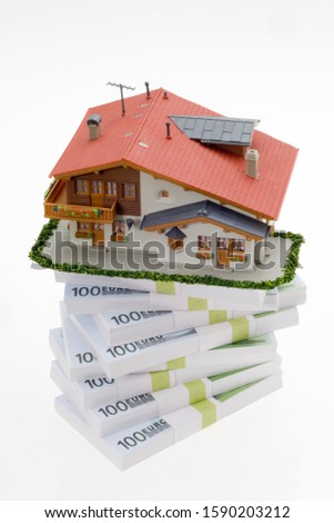 Model of residential house on stack of European currency