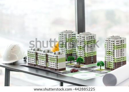 Model of residential quarter and hardhats on table in office