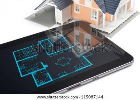 Model of the house and digital tablet with interior blueprint (corresponding with model) on screen. Architect's workplace.