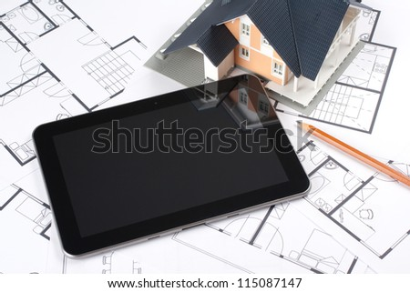Model of the house on blueprints, digital tablet and pencil. Architect's workplace. Choose from interior variants. You may place your own screen, for example web page on tablet screen.