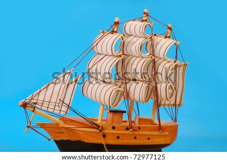 model of vintage tall sailing ship against blue background