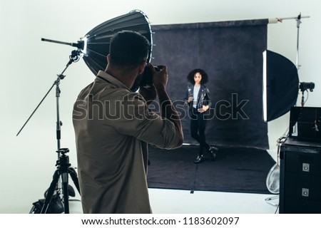 Model posing for a photograph during a photo shoot. Studio shot of a photographer shooting photos of a woman with studio flash lights on.
