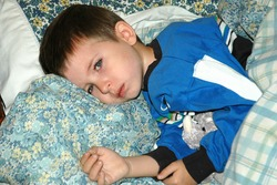 Model released image of young caucasian preschool age boy laying on pillows looking ill, not feeling good, not happy, sad