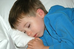 Model released image of Young preschool age boy sleeping on a white pillow wearing blue pajamas