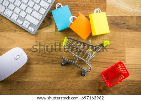 Model shopping bag, basket and shopping cart on wooden floor with computer keyboard and mouse. Shopping at home or online internet shopping e-commerce idea concept.