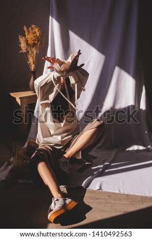 Model sitting and wearing casual outfit. Milky blouse, beige or brown pants and sneakers in trendy minimalistic style. Hands up. Figure from female hands. Woman wear blouses with tape on sleeves.
