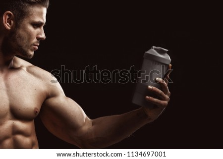 Model sports young man on dark background. Portrait of sporty strong muscle  guy with protein de74644e4e
