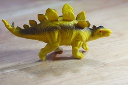 Model toy on a dinosaur of Stegosaurus on a wooden table for selective focus under the light from lamp.A genus of herbivorous thyreophoran dinosaur and this genus date to the Late Jurassic period.