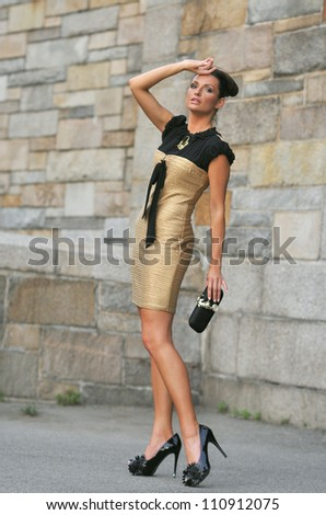 Model wearing couture designer clothes and holding couture designer purse with watch on it - stock photo