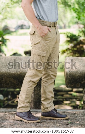 Model wearing yellow brown  color cargo pants or cargo trousers #1395151937