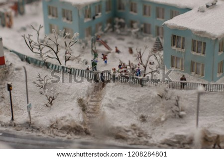 model with a picture of a miniature, where people in front of the school people clean the snow with shovels,and children play snowballs and sculpt snowmen