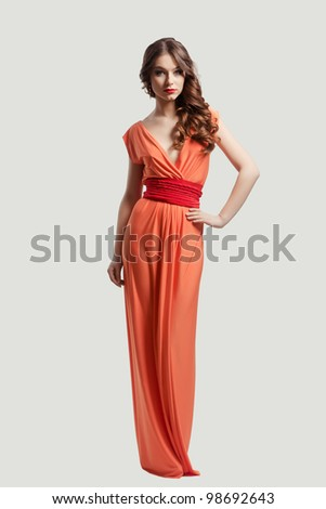 Model with beautiful long hair posing in orange dress isolated