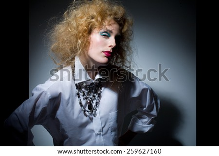 Model with fluffy hair wearing white shirt and jewelry.