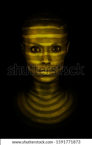 Model with golden glowing make-up posing in studio. Portrait of a young woman with lines, drawn on the face. Isolated on black background.
