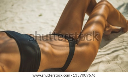 model with picture-postcard body in black bikini lying in a sexy pose in shade